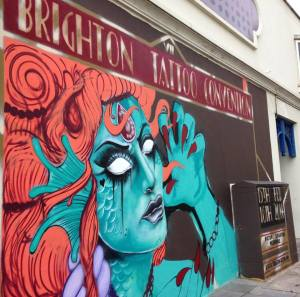 The wall mural on the side of the hotel  Brighton Tattoo Convention - Hilton Brighton Metropole, painted by Sinna One